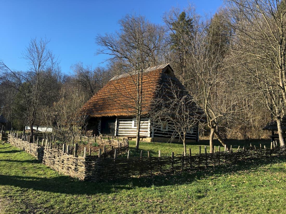 Drewniana chata z dachem krytym strzecha w skansenie w sanoku