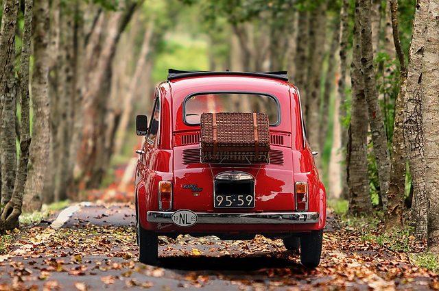 Czerwony stary samochód na jesiennej drodze