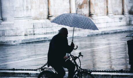 mezczyzna adacy rowerem z parasolką w deszczu (1)